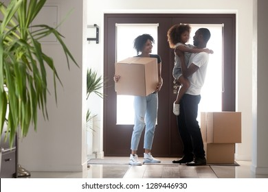 Happy black family with kid girl holding box entering into own house on moving day, african american parents and child standing in hallway, mortgage, relocation, tenants welcome to new home concept