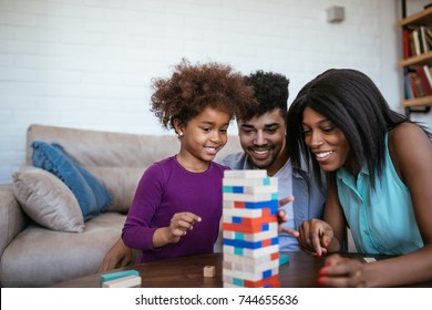 A happy black family palying a round of jenga with their lovely daughter.