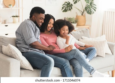 Happy black father, mother and their little daughter relaxing with smartphone at home together, sitting on couch, watching videos or making video call