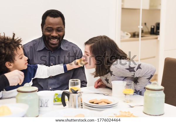Happy black father with young children having breakfast, mixed-race family having fun in the kitchen, the little boy plays and feeds his sister and daddy looks them and smiles