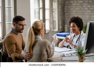 Happy black female doctor counselling a couple about their medical treatment at clinic.