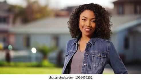 Happy black female youth in denim jacket smiling at camera outside home