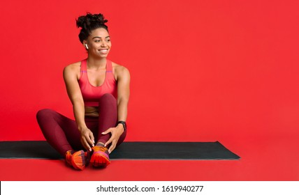 Happy black fitness girl resting on yoga mat during training, enjoying music with earbuds, copy space