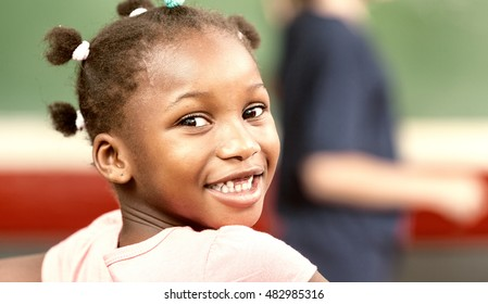 Happy black girl in elementary classroom.