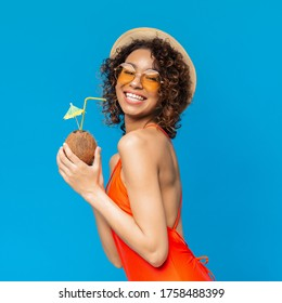 Happy black girl in swimsuit enjoying exotic summer coconut cocktail and smiling at camera, posing over blue background in studio, copy space