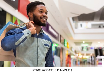 Happy black guy in shopping mall, panorama, copy space