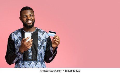 Happy black guy shopping online, using mobile phone. Smiling african american man in traditional costume with smartphone showing credit card over pink studio background, panorama with copy space