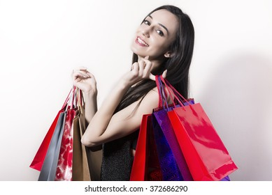 Happy black haired and black dressed woman with shopping bags.