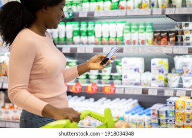 Happy black lady checking her smartphone shopping app while purchasing groceries at dairy section of big mall, copy space. Young African American woman buying foodstuff at supermarket
