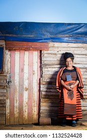 Happy black lady standing against a shack while wearing traditional clothes