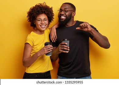 Happy black male student prouds of himself as passed exam successfully, drinks takeaway coffee with female groupmate, enjoy spare time after classes, have hot drink, isolated over yellow wall