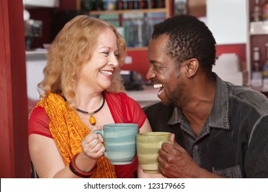 Happy Black man and European woman laughing together in cafe