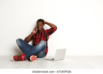 Happy black man having a pleasant phone call while resting from work with laptop. African-american boy at white studio background sitting with crossed legs