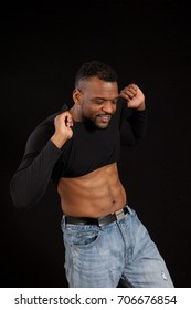 Happy Black man in black shirt  with a smile as he pulls his shirt up