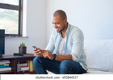 Happy black man using smart phone at home. Smiling young african man at home sitting on couch reading phone message. Handsome american guy download app for his mobile phone.
