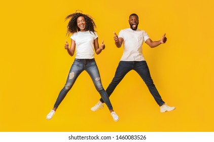 Happy Black Man And Woman Are Jumping In The Air And Showing Thumbs Up, yellow background