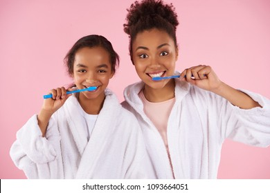 Happy black mother and daughter in dressing gown brush teeth. Dental hygiene concept. Isolated on pink background. Studio portrait.
