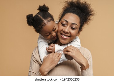 Happy black mother and daughter hugging while making fun together isolated over beige background