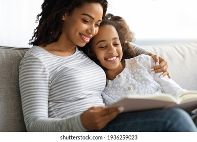 Happy black mother and daughter reading book together