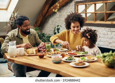 Happy black parents and their daughter eating at dining table at home.