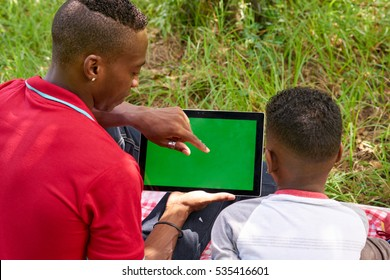 Happy black people in city park. African american family with young man and child using tablet computer for internet. Laptop monitor with green screen