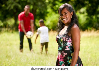 Happy black people in park. African american family with young father and son having fun with football. Portrait of mother smiling