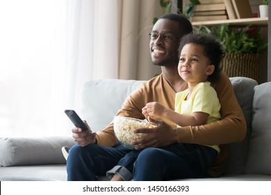 Happy black single father and cute little son sit on couch relax watching TV eating popcorn together, smiling african American dad and preschooler child enjoy family weekend with snack and cartoon