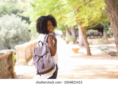 Happy black woman with backpack walking in park, turning head backward and smiling at camera. Afro American tourist travelling alone and seeing sights. Solo travel and excursion concept