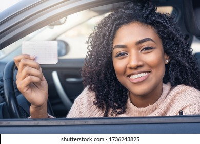 Happy black woman driving her new car holding car license
