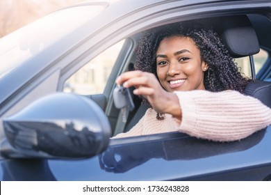 Happy black woman driving her new car holding key