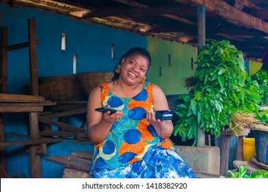 happy black woman sitting in the market with vegetables on the table and she's holding a phone and a pos machine