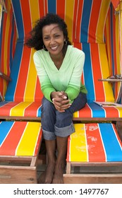 Happy black woman sitting outdoors in the beachchair