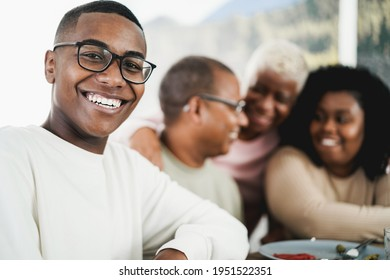 Happy black young man eating lunch with his family at home - Father, daughter, son and mother having fun together sitting at dinner table - Focus on boy face