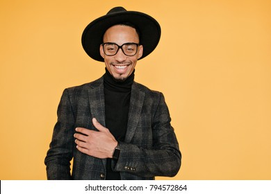 Happy black young man wears elegant dark suit posing with pleased smile. Indoor photo of relaxed africans male model in glasses enjoying photoshoot.
