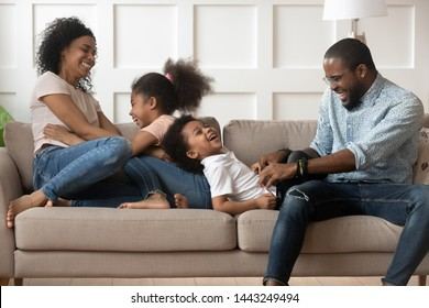 Happy black young parents relax on couch with preschooler kids tickling laughing together, playful african American family have fun at home together rest playing with children on sofa