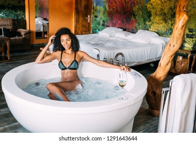 Happy black young woman relaxing in the hydro massage bath