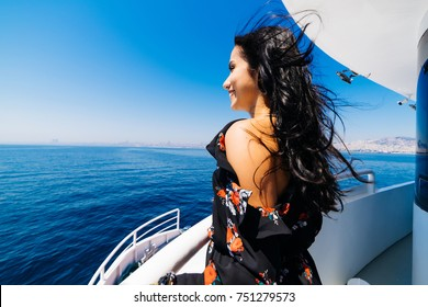 happy black-haired girl in a fashionable dress is standing on a yacht, looking at the ocean