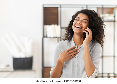Happy blessed African American teenage girl with curly hair talking on mobile phone and laughing, expressing positive emotions, or a young joyful businesswoman is having a pleasant conversation