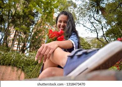 Happy blissful and in love. This beautiful brunette has just been given a bouquet of red roses and her happiness is raining throughout the park