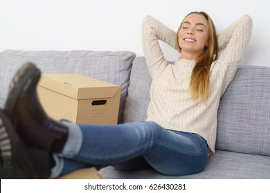 Happy blissful young woman relaxing on a sofa with her hands behind her head, eyes closed and feet up on a table