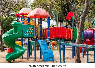 happy blond boy, child climb on colourful outdoor playground equipment in park.