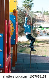 Happy blond boy hang on pipe of playground. Caucasian child in sunshine.