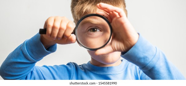 happy blond boy looking through a magnifying glass. concept of curiosity with respect to life, search for details and clues, investigating, digging observe