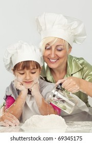 Happy blond caucasian mother and daughter preparing dough and having fun