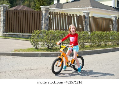 Happy blond child girl learning how to ride bicycle near house in village