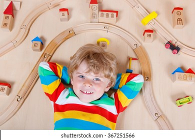 Happy blond child playing wooden trains and roalroad indoor. Active kid boy wearing colorful shirt and having fun with building and creating.