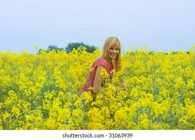happy blond girl enjoying in a yellow field and smiling