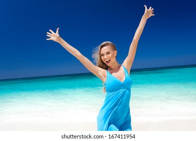 Happy blond girl on beach, feeling freedom. Vacation concept