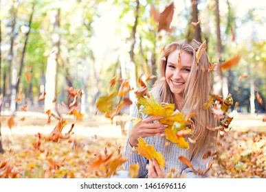 Happy blond girl posing in autumn park on yellow trees background. Have fun with autumn leaves