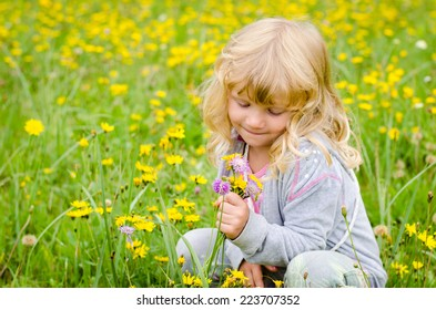 happy blond girl smelling yellow flowers